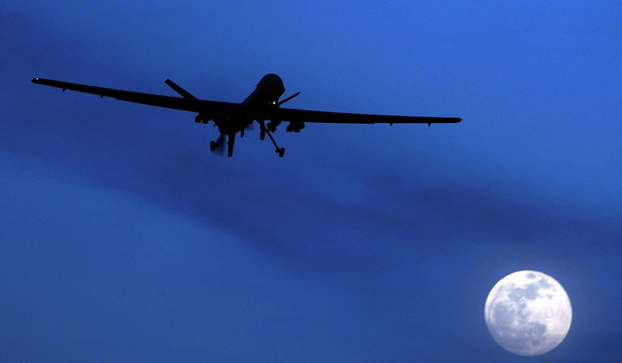 FILE - In this Jan. 31, 2010 file photo, an unmanned U.S. Predator drone flies over Kandahar Air Field, southern Afghanistan, on a moon-lit night. The deaths of an Italian and an American in a covert CIA drone strike in Pakistan have breathed new urgency into a long-stalled plan to give the Pentagon primacy over targeted killing of terrorists overseas.   (AP Photo/Kirsty Wigglesworth, File)