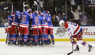 Washington Capitals left wing Curtis Glencross (22) skates past the New York Rangers as they celebrate their 2-1 overtime victory over the Capitals during Game 5 in the second round of the NHL Stanley Cup hockey playoffs, Friday, May 8, 2015, in New York. (AP Photo/Kathy Willens)