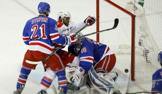 Washington Capitals right wing Joel Ward, middle, collides with New York Rangers goalie Henrik Lundqvist (30) as he knocks the puck into the goal near New York Rangers center Derek Stepan (21) during the second period of Game 5 in the second round of the NHL Stanley Cup hockey playoffs, Friday, May 8, 2015, in New York. The goal was waved off by the officials because of contact made with the goalie. (AP Photo/Julie Jacobson)