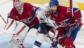 Montreal Canadiens goalie Carey Price, left, tries to look past Tampa Bay Lightning's Brenden Morrow and Canadiens defenseman Tom Gilbert during the second period of Game 5 of a second-round NHL Stanley Cup hockey playoff series Saturday, May 9, 2015, in Montreal. (Paul Chiasson/The Canadian Press via AP) MANDATORY CREDIT
