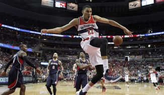 Washington Wizards forward Otto Porter Jr. (22) celebrates his dunk in front of Atlanta Hawks forward Paul Millsap (4), forward Pero Antic (6), from Macedonia, and guard Jeff Teague (0) in the second half of Game 3 of the second round of the NBA basketball playoffs Saturday, May 9, 2015, in Washington. The Wizards won 103-101. (AP Photo/Alex Brandon)