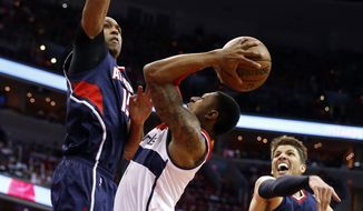 Washington Wizards guard Bradley Beal (3) tries to shoot between Atlanta Hawks center Al Horford (15), from the Dominican Republic, and guard Kyle Korver (26) in the first half of Game 3 of the second round of the NBA basketball playoffs Saturday, May 9, 2015, in Washington. (AP Photo/Alex Brandon)