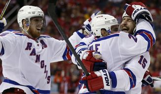 New York Rangers defenseman Marc Staal (18), defenseman Dan Boyle (22) and left wing Tanner Glass (15) celebrate the game winning goal by Boyle, during the third period of Game 6 in the second round of the NHL Stanley Cup hockey playoffs against the Washington Capitals, Sunday, May 10, 2015, in Washington. The Rangers won 4-3. (AP Photo/Alex Brandon)