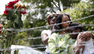 Area residents Alberta Harris, center, and Waynetta Theodore, left, and Christiena Preston, console each other as they pay their respects at a makeshift memorial, near the site where two Mississippi police officers were killed, Sunday, May 10, 2015, in Hattiesburg, Miss. The officers were shot to death during an evening traffic stop turned violent, a state law enforcement spokesman said Sunday. Three suspects were in custody, including two who are charged with capital murder. (AP Photo/Rogelio V. Solis)