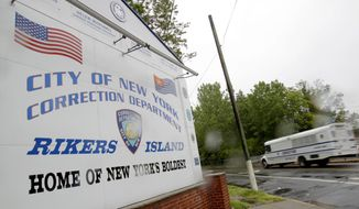 A bus drives past the the entrance to Rikers Island in New York in this May 17, 2011, file photo. (AP Photo/Seth Wenig, File)