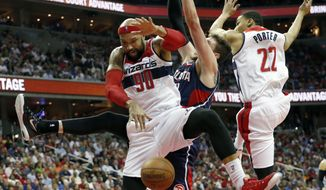 Washington Wizards forward Drew Gooden (90), Atlanta Hawks forward Mike Muscala and Wizards' Otto Porter Jr. (22) collide under the basket in the second half of Game 4 of the second round of the NBA basketball playoffs Monday, May 11, 2015, in Washington. The Hawks won 106-101. (AP Photo/Alex Brandon)