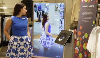 In this photo taken Wednesday, April 15, 2015, sales manager Alysa Stefani demonstrates the Memory Mirror at the Neiman Marcus store in San Francisco's Union Square. The mirror is outfitted with sensors, setting off motion-triggered changes of clothing. The mirror also doubles as a video camera, capturing a 360 degree view of what an outfit looks like and making side-by-side comparisons. (AP Photo/Eric Risberg)
