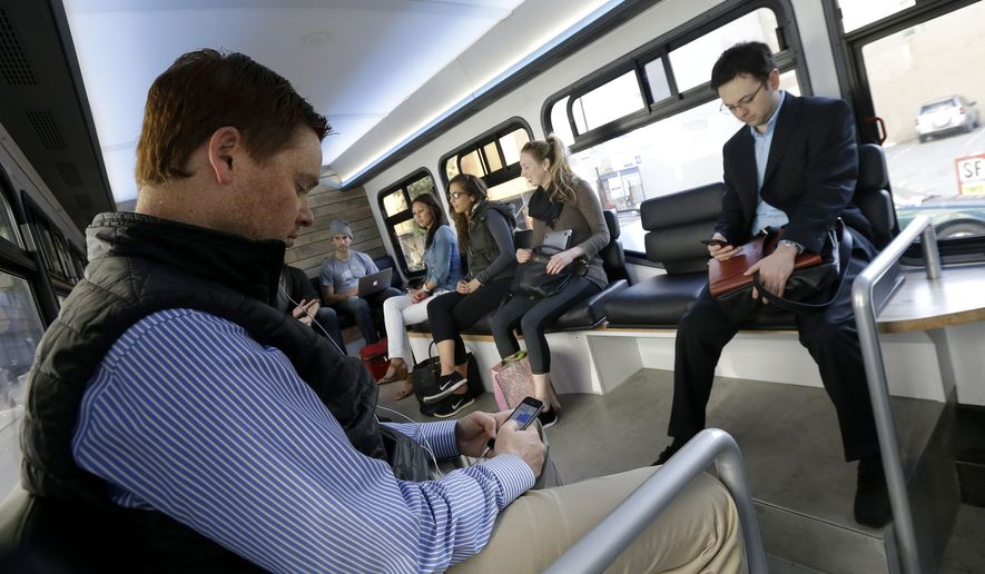 In this April 14, 2015 photo, Leap commuters use their smartphones during a bus ride in San Francisco. A company called Leap, a bus company that offers rides with spacious seating, free Wi-Fi and attendants who deliver snacks, launched the service last month with morning and evening commutes that follow public bus routes between the tony Marina district and the heart of downtown San Francisco. (AP Photo/Jeff Chiu)