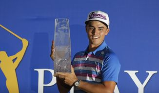 Rickie Fowler holds The Players Championship trophy, Sunday, May 10, 2015, in Ponte Vedra Beach, Fla. Fowler won in a sudden death playoff against Kevin Kisner. (AP Photo/Chris O'Meara)