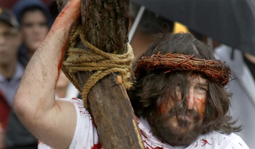 A volunteer from Bridgewater Community Churches portrays Jesus as he carries a cross during the annual reenactment of the crucifixion of Jesus on Good Friday on April 3 in Bridgewater, Pa. (Associated Press)