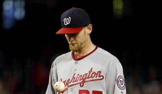 Washington Nationals pitcher Stephen Strasburg tosses the baseball after giving up a three run home run to Arizona Diamondbacks Mark Trumbo during the fourth inning of a baseball game, Tuesday, May 12, 2015, in Phoenix. (AP Photo/Matt York)