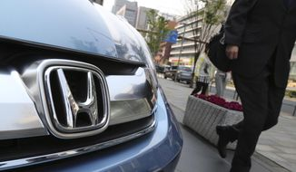 A man walks past a Honda on display at Honda Motor Co. headquarters in Tokyo in this April 25, 2014, file photo. Honda Motor Co. recalled an additional 4.89 million vehicles around the world Thursday, May 14, 2015, for a new type of problem in Takata air bag inflators, for which Japanese rivals Toyota and Nissan have already carried out recalls.(AP Photo/Koji Sasahara, File)