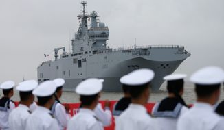 Soldiers from the People's Liberation Army navy stand guard as the Dixmude, the third French Mistral-class amphibious assault ship, arrives at Wusong military dockyard, in Shanghai, China. (Associated Press)
