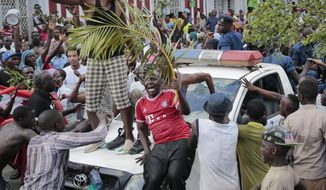 Demonstrators, some holding palm leaves as a peace sign, celebrate what they perceive to be an attempted military coup d'etat, as they surround a police truck in the capital Bujumbura, Burundi Wednesday, May 13, 2015. Police vanished from the streets of Burundi's capital Wednesday as thousands of people celebrated a rumored coup attempt against President Pierre Nkurunziza. (AP Photo/Berthier Mugiraneza)