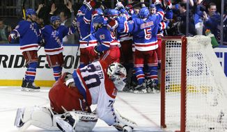 FILE - In this May 13, 2015, file photo, the New York Rangers celebrate the game winning goal by center Derek Stepan (21) against the Washington Capitals as Capitals goalie Braden Holtby looks at the puck in the net in overtime of Game 7 of the Eastern Conference semifinals during the NHL hockey Stanley Cup playoffs in New York. The Rangers won 2-1. The NHL's final four teams are 19-5 at home in the playoffs.  (AP Photo/Kathy Willens, File)