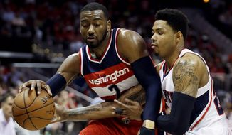 Washington Wizards' John Wall, left, dribbles against Atlanta Hawks' Kent Bazemore in the third quarter of Game 5 of the second round of the NBA basketball playoffs Wednesday, May 13, 2015, in Atlanta. (AP Photo/John Bazemore)