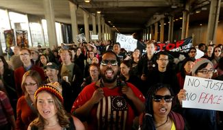 Demonstrators walk in a tunnel under the Monona Terrace Convention Center while making their way along John Nolen Drive during a rally for Tony Robinson in Madison, Wis., Wednesday, May 13, 2015. (John Hart/Wisconsin State Journal via AP)