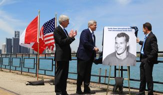 Michigan Gov. Rick Snyder, left, and Canada Prime Minister Stephen Harper and Murray Howe, right, Gordie Howe's son, unveil a portrait of the hall of famer during a news conference, Thursday, May 14, 2015, in Windsor, Ontario, announcing that a planned bridge connecting Detroit and Windsor, will be named after the hockey great. The yet-to-be built Gordie Howe International Bridge is expected to be operational in 2020.  (Dave Chidley/The Canadian Press via AP) MANDATORY CREDIT