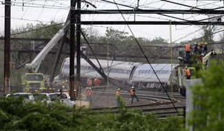 A crane raises the end of a derailed train car as emergency personnel work at the scene of a deadly train wreck, Wednesday, May 13, 2015, in Philadelphia. An Amtrak train headed to New York City derailed and crashed in Philadelphia on Tuesday night killing at least seven people and injuring dozens more. (AP Photo/Mel Evans)