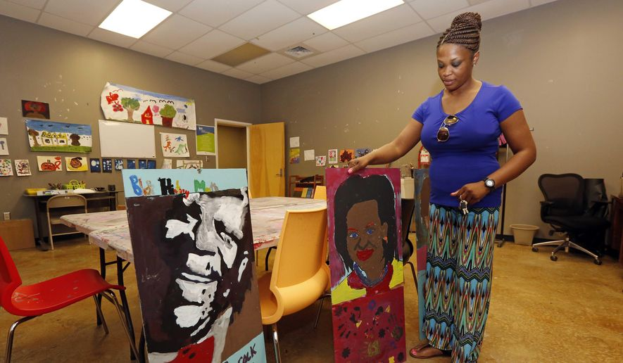 B.B. King Museum and Delta Interpretive Center education coordinator, April Brock, shows off portraits  Rosa Parks, Michelle Obama and B.B. King, in Indianola, Miss. that students painted during Black History Month.(AP Photo/Rogelio V. Solis)