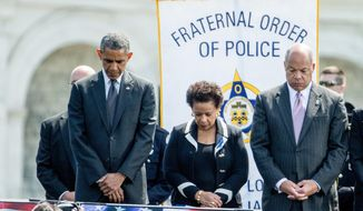President Barack Obama, Attorney General Loretta Lynch, and Homeland Security Secretary Jeh Johnson stand for a moment of silence at the 34th Annual National Peace Officers Memorial Service, Friday, May 15, 2015, on the West Front of the Capitol in Washington. The ceremony honors all law enforcement officers who died in the line of duty.  (AP Photo/Andrew Harnik)