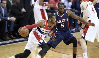 Washington Wizards guard John Wall (2) dribbles against Atlanta Hawks forward DeMarre Carroll (5) in the first half of Game 6 of the second round of the NBA basketball playoffs, Friday, May 15, 2015, in Washington. (AP Photo/Nick Wass)