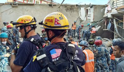 In this May 12, 2015 photo provided by the U.S. Agency for International Development, Los Angeles County Fire Department urban search and rescue team memebrs work to recover survivors from a four-story building that collapsed in this week's earthquake in Singati, a mountain village in Nepal. Tuesday's temblor was an aftershock to the April 25 main Gorkha earthquake that's killed more than 8,000 people. The Disaster Assistance Response Team included 57 urban search and rescuers each from Los Angeles County and Fairfax County, Va. (Kashish Das/USAID/via AP)