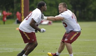 Washington Redskins offensive tackle Tovar Allen, left,  blocks offensive lineman and first round draft pick Brandon Scherff, right, during NFL football rookie minicamp, Saturday, May 16, 2015, at Redskins Park in Ashburn, Va. (AP Photo/Luis M. Alvarez)