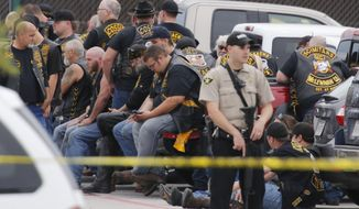 "A McLennan County deputy stands guard near a group of bikers in the parking lot of a Twin Peaks restaurant Sunday, May 17, 2015, in Waco, Texas. Waco Police Sgt. W. Patrick Swanton told KWTX-TV there were ""multiple victims"" after gunfire erupted between rival biker gangs at the restaurant. (Rod Aydelotte/Waco Tribune-Herald via AP)"