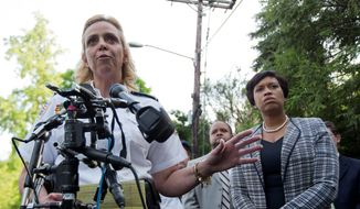 D.C. Police Chief Cathy Lanier (left) with Mayor Muriel Bowser, said that police are seeking a man seen in a brief surveillance video for questioning in connection with a fire at a home in Northwest Washington, Thursday, where four people were found dead. (Associated Press)