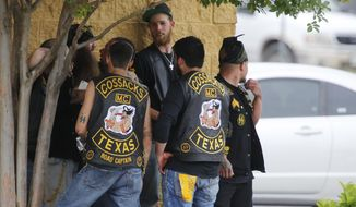 Bikers congregate against a wall while authorities investigate a Twin Peaks restaurant Sunday, May 17, 2015, in Waco, Texas. (Rod Aydelotte/Waco Tribune-Herald via AP)