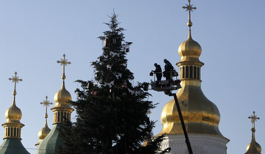 Workers decorate a New Year tree, in front of the St. Sophia Cathedral in central Kiev, Ukraine, Monday, Dec. 15, 2014. New Year is widely celebrated as the most popular holiday in Ukraine with the Orhodox Christmas being celebrated on Jan. 7. (AP Photo/Sergei Chuzavkov)