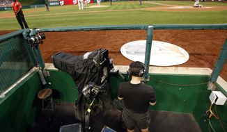 A MASN network videographer checks his phone after technical problems forced the network to use a different feed for several innings of a baseball game between the Washington Nationals and the Philadelphia Phillies at Nationals Park Saturday, Aug. 2, 2014, in Washington. (AP Photo/Alex Brandon)
