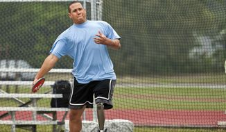 In this photo provided by Eglin Air Force Base Public Affairs shows Brian Williams, an Air Force Wounded Warrior athlete as prepares to throw the discus during introductory adaptive sports and rehabilitation camp at Eglin Air Force Base, Fla., April 14, 2015. Airmen  gathered in the Florida Panhandle for a training camp hoping to defeat the Army, Marines and Navy next month at the 2015 Department of Defense Wounded Warrior Games in Quantico, Virginia. (Samuel King Jr. /Eglin Air Force Base via AP)
