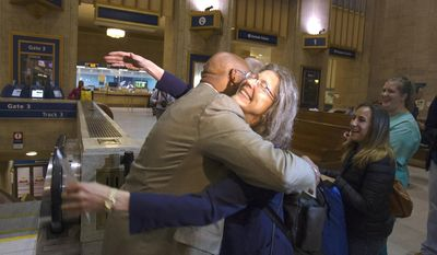 Philadelphia Mayor Michael Nutter hugs Mary Schaheen, the first passenger in line for Train 110 at Philadelphia's 30th Street Station, Monday, May 18, 2015, as Amtrak trains began rolling on the busy Northeast Corridor early Monday, the first time in almost a week following a deadly crash in Philadelphia. (AP Photo/Michael R. Sisak)