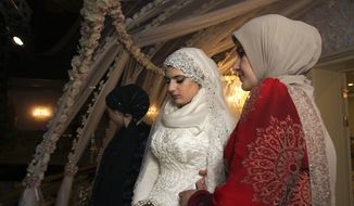 Chechen Kheda Goilabiyeva, second right, stands after her wedding with Chechen police officer Nazhud Guchigov, in Chechnya's provincial capital Grozny, Russia, Saturday, May 16, 2015. A 46-year-old Chechen police officer taking a 17-year-old as his second wife in flagrant violation of Russian laws has caused a storm in the Russian media and put the region's ruler on the defensive. (AP Photo, File)