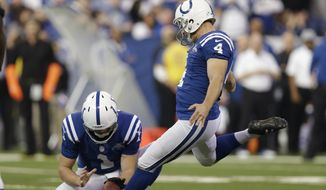 Indianapolis Colts' Adam Vinatieri (4) kicks an extra point out of the hold of Pat McAfee (1) during the first half of an NFL football game against the Jacksonville Jaguars Sunday, Dec. 29, 2013, in Indianapolis. (AP Photo/Michael Conroy)