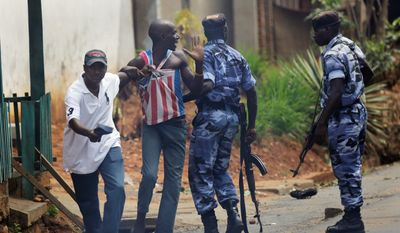 Police and a member of the Intelligence Services in civilian clothes detain a protester in the Nyakabyga neighborhood of Bujumbura, Burundi. Police fired live rounds and tear gas to disperse demonstrators protesting the president's seeking a third term. (associated press)