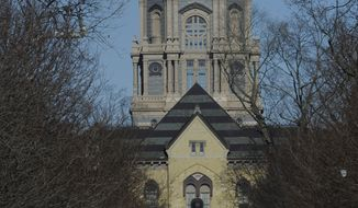 FILE - In this Jan. 17, 2013 file photo, people walk in front of the Notre Dame administration building, known as the Golden Dome, on the campus of the University of Notre Dame in South Bend, Ind. The University of Notre Dame is suing the Obama administration over a federal mandate that its health insurance plans for students and employees cover birth control. The university filed its lawsuit Tuesday, Dec. 3, 2013, in U.S. District Court in South Bend.  (AP Photo/Joe Raymond, FILE)