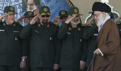 In this picture released by an official website of the office of the Iranian supreme leader on Wednesday, May 20, 2015, Supreme Leader Ayatollah Ali Khamenei, right, arrives at a graduation ceremony of the Revolutionary Guard's officers, while deputy commander of the Revolutionary Guard, Hossein Salami, second right, former commanders of the Revolutionary Guard Mohsen Rezaei, second left, and Yahya Rahim Safavi salute him in Tehran, Iran. Iran's supreme leader vowed Wednesday he will not allow international inspection of Iran's military sites or access to Iranian scientists under any nuclear agreement with world powers. (Office of the Iranian Supreme Leader via AP)