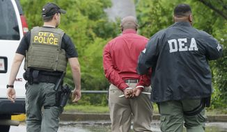 An unidentified man, center, is escorted from a medical clinic in Little Rock, Ark., by Drug Enforcement Administration officers Wednesday, May 20, 2015. Early morning raids in Arkansas, Alabama, Louisiana and Mississippi were the final stage of an operation launched last summer by the DEA's drug diversion unit, a senior DEA official said, speaking on condition of anonymity. (AP Photo/Danny Johnston) ** FILE **