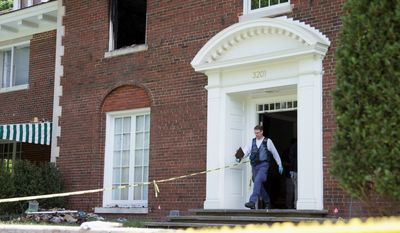 A Bureau of Alcohol, Tobacco, Firearms and Explosives investigator walks out of the fire-damaged multimillion-dollar home in northwest D.C. News reports indicate the family was held captive in the home the night before the fire and that $40,000 in cash was delivered to the residence shortly before the fire was set.