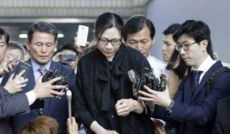 Former Korean Air executive Cho Hyun-ah, center, is surrounded by reporters as she leaves the Seoul High Court in Seoul, South Korea, Friday, May 22, 2015. The upper court Friday sentenced Cho to 10 months in prison and then suspended the sentence for two years. (AP Photo/Lee Jin-man)
