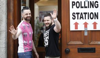 Partners Adrian, left and Shane, arrive to vote at a polling station in Drogheda, Ireland, Friday, May 22, 2015.  Ireland began voting Friday in a referendum on Gay marriage which will require an amendment to the Irish constitution. (Associated Press) ** FILE **