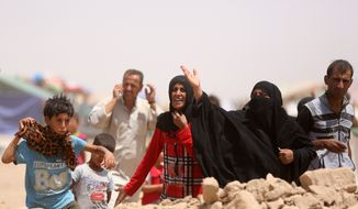 Displaced civilians from Ramadi and surrounding areas stand in a camp in the town of Amiriyat al-Fallujah, west of Baghdad, Iraq, Friday, May 22, 2015. (Associated Press) ** FILE **