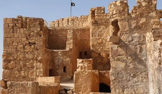 The Islamic State militants flag, top center, is raised on the to top of Palmyra castle, in the Syrian town of Palmyra, Syria, May 22, 2015. (Associated Press) ** FILE **