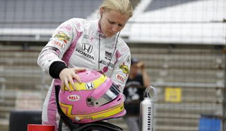 FILE- In this May 11, 2015 file photo, Pippa Mann, of the United Kingdom, prepares to drive during practice for the Indianapolis 500 auto race at the Indianapolis Motor Speedway in Indianapolis.  Mann rattled off the list of body parts still aching after a brutal crash at Indianapolis 500 practice. Her right foot, her right ankle. Her ribs. She has more bruises than most fighters do after a few rounds in the octagon. Hobbled, yet hopeful, Mann is still in the cockpit, prepping for the most prestigious race in auto racing. (AP Photo/Michael Conroy, File)
