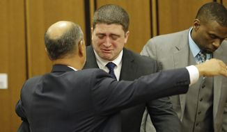 Michael Brelo hugs his attorney, Patrick D'Angelo, after the verdict in his trial Saturday, May 23, 2015, in Cleveland. Brelo, a patrolman charged in the shooting deaths of two unarmed suspects during a 137-shot barrage of gunfire was acquitted Saturday in a case that helped prompt the U.S. Department of Justice determine the city police department had a history of using excessive force and violating civil rights. (AP Photo/Tony Dejak)