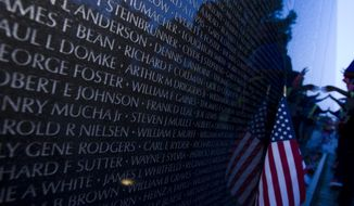 Visitors touch the names at the wall of Vietnam Veterans Memorial during a Memorial Day candlelight vigil at the Vietnam Veterans Memorial in Washington, DC., Friday, May 22, 2015.  (AP Photo/Jose Luis Magana)