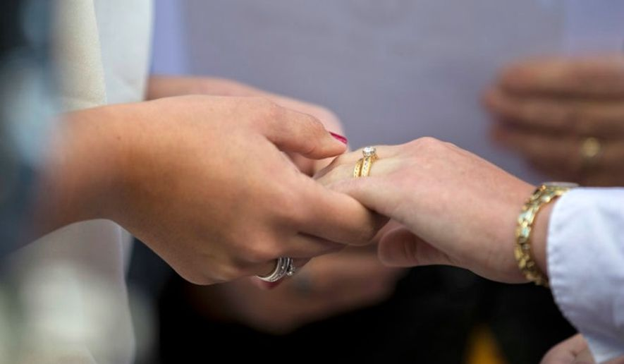 two women exchange vows during a wedding ceremony associated press file - Gay Wedding Rings